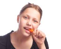 Muchacha diez que come la zanahoria Imagenes de archivo