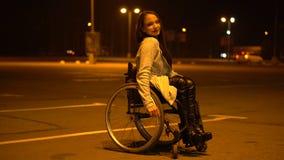 Muchacha discapacitada atractiva en un taxi que espera de la silla de ruedas para en el estacionamiento de la noche cerca de la a almacen de video