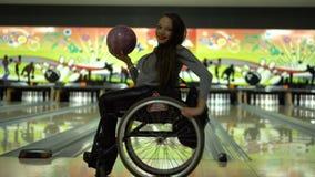 Muchacha discapacitada atractiva en una silla de ruedas que se divierte en los bolos, baile con una bola de bolos metrajes