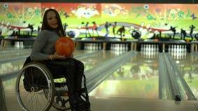 Muchacha discapacitada atractiva en una silla de ruedas que se divierte en los bolos, baile con una bola de bolos almacen de metraje de vídeo