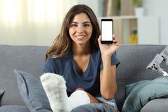 Muchacha discapacitada con el pie del yeso que muestra la pantalla del teléfono Fotografía de archivo libre de regalías