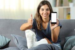 Muchacha discapacitada que muestra la pantalla del teléfono con los pulgares para arriba Fotos de archivo libres de regalías