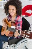 Muchacha discapacitada que toca la guitarra Imagen de archivo