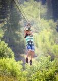 Muchacha diversa sonriente que monta un zipline a través del bosque Imagenes de archivo