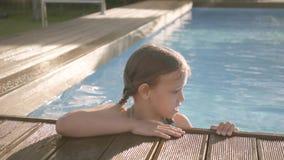 Muchacha divertida adorable con la risa de las coletas, mostrando el pulgar encima de la mirada fuera de la piscina, aferrándose  almacen de metraje de vídeo