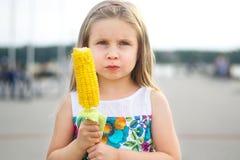 Muchacha divertida adorable que come el maíz en la mazorca en día de verano soleado Fotos de archivo libres de regalías