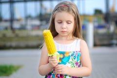 Muchacha divertida adorable que come el maíz en la mazorca en día de verano soleado Imagen de archivo libre de regalías