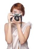 Muchacha divertida atractiva con una cámara sobre blanco imágenes de archivo libres de regalías