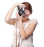 Muchacha divertida atractiva con una cámara sobre blanco fotografía de archivo libre de regalías