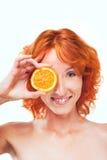Muchacha divertida con el pelo rojo que lleva a cabo la rebanada de naranja Fotos de archivo