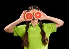 Muchacha divertida con el pomelo cortado en ojos Imagenes de archivo