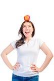 Muchacha divertida con la manzana en su cabeza Imagen de archivo