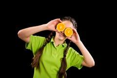 Muchacha divertida con la naranja cortada en ojos Foto de archivo libre de regalías