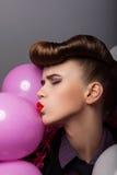 Muchacha divertida con los balones de aire coloridos que hace muecas Fotos de archivo