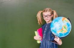 Muchacha divertida con los libros y el globo que se colocan cerca de la pizarra verde vacía Imagen de archivo