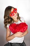 Muchacha divertida con los vidrios y la almohada rojos del corazón Fotos de archivo