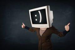 Muchacha divertida con una caja del monitor en su cabeza y una cara sonriente Imágenes de archivo libres de regalías