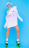 Muchacha divertida de la moda en sudadera con capucha y medias coloreadas en un backgr azul Imagenes de archivo