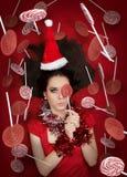 Muchacha divertida de la Navidad que sostiene un caramelo rodeado por las piruletas Imagen de archivo