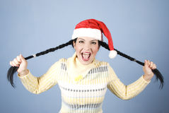 Muchacha divertida de Navidad que tira de las coletas Imagenes de archivo