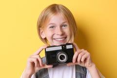 Muchacha divertida del adolescente con la cámara en fondo amarillo Imagen de archivo libre de regalías