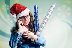 Muchacha divertida del inconformista en el sombrero de la Navidad que hace el teléfono Imagen de archivo libre de regalías