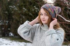Muchacha divertida del inconformista en suéter y casquillo hechos punto Imagen de archivo
