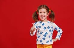 Muchacha divertida del niño en vidrios en fondo coloreado Imágenes de archivo libres de regalías