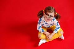 Muchacha divertida del niño en vidrios en fondo coloreado Foto de archivo