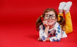 Muchacha divertida del niño en vidrios en fondo coloreado Fotografía de archivo