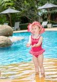 Muchacha divertida del pequeño niño cerca de la piscina en centro turístico tropical en Tailandia, Phuket Foto de archivo