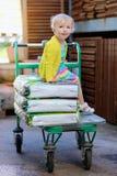 Muchacha divertida del preescolar que se sienta en la carretilla de las compras Foto de archivo