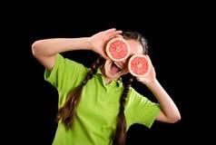 Muchacha divertida emocionada con el pomelo cortado en ojos Imagenes de archivo