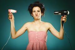 Muchacha divertida en bigudíes con el hairdryer que diseña el pelo Imagen de archivo libre de regalías