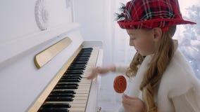 Muchacha divertida en el sombrero rojo que juega música en piano y que sostiene la piruleta a disposición almacen de metraje de vídeo