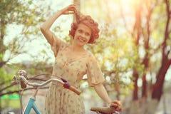 Muchacha divertida en la bicicleta en parque de la primavera Foto de archivo libre de regalías