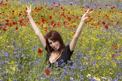 Muchacha divertida en las flores imagenes de archivo