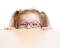 Muchacha divertida en las lentes que ocultan detrás de la tabla Imagen de archivo libre de regalías