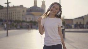 Muchacha divertida en los auriculares blancos grandes que engañan alrededor y que se divierten 4K metrajes
