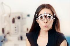 Muchacha divertida en los vidrios de la prueba del ojo del examen que llevan oftalmológico Imagen de archivo libre de regalías