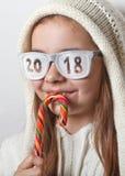 Muchacha divertida en sombrero con el caramelo y los vidrios con la inscripción 2018 Imagenes de archivo