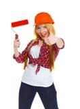 Muchacha divertida en un casco con el rodillo a disposición se aísla en Imagen de archivo