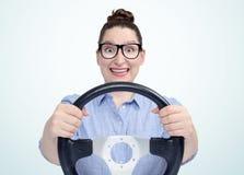 Muchacha divertida en vidrios con el volante del coche, concepto auto Imagen de archivo libre de regalías