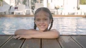 Muchacha divertida feliz adorable en las gafas de sol amarillas que miran en la cámara que sonríe, mirando fuera de la piscina, a metrajes