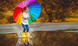 Muchacha divertida feliz del niño con el paraguas que salta en charcos en rubb imagenes de archivo
