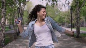Muchacha divertida feliz que camina abajo de la calle y que baila mientras que escucha la música en los auriculares metrajes