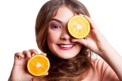 Muchacha divertida hermosa joven con la rebanada y el maquillaje anaranjados y peinado que mira la cámara Foto de archivo libre de regalías
