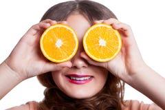 Muchacha divertida hermosa joven con la rebanada y el maquillaje anaranjados y peinado que mira la cámara Imagen de archivo libre de regalías