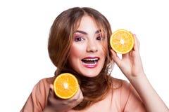 Muchacha divertida hermosa joven con la rebanada y el maquillaje anaranjados y peinado que mira la cámara Imagen de archivo