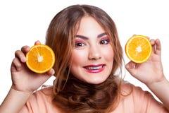 Muchacha divertida hermosa joven con la rebanada y el maquillaje anaranjados y peinado que mira la cámara Imágenes de archivo libres de regalías